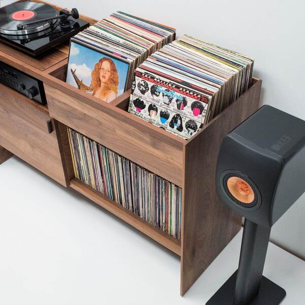Unison Walnut Record Stand with flip-style LP storage bins, vibration isolated record player platform, and audio cabinet room for hi-fi sound equipment. Features a rich natural walnut wood finish. Displayed with turntable sitting on top and standing Bluetooth powered speakers on either side against a wall.